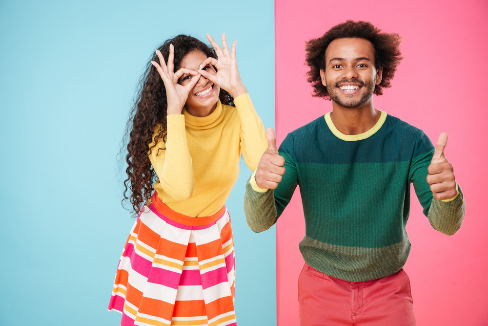 Funny african young couple having fun and showing thumbs up over colorful background