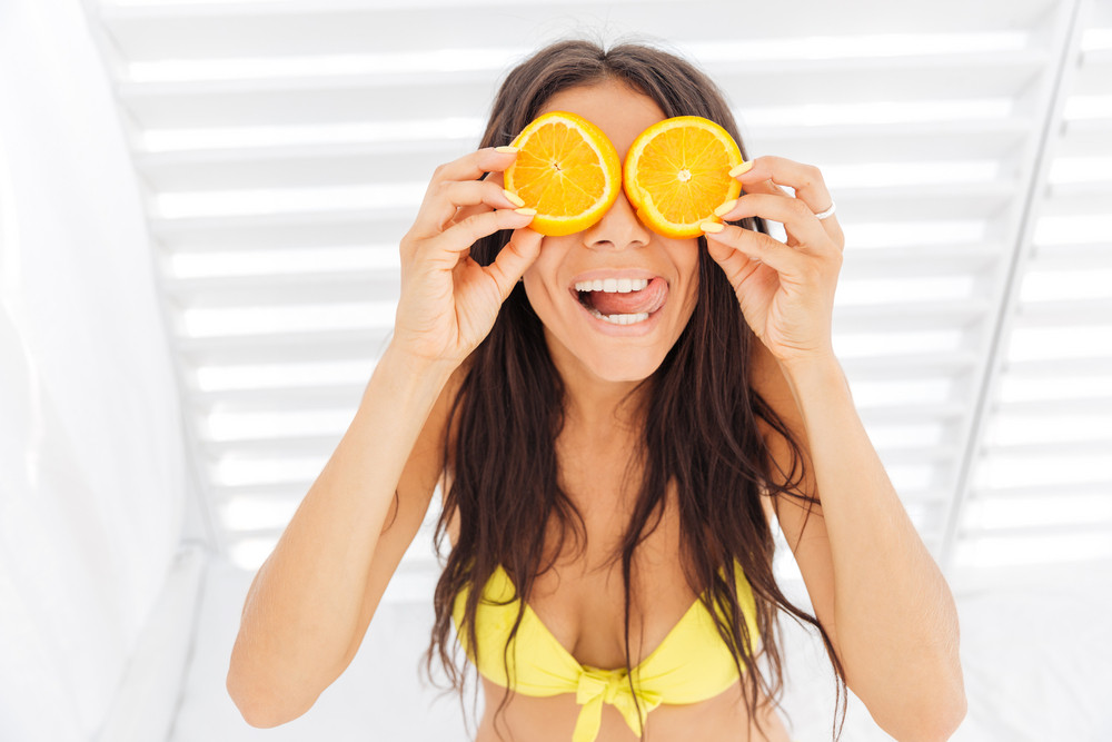 Funny cheerful young woman in bikini holding two halves of orange against her eyes over white background