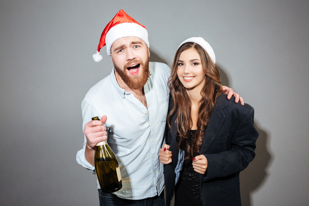 Funny Christmas Couple With Champagne Looking At Camera