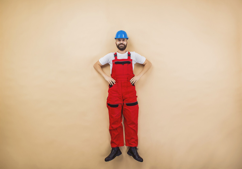 Funny construction worker is posing in studio