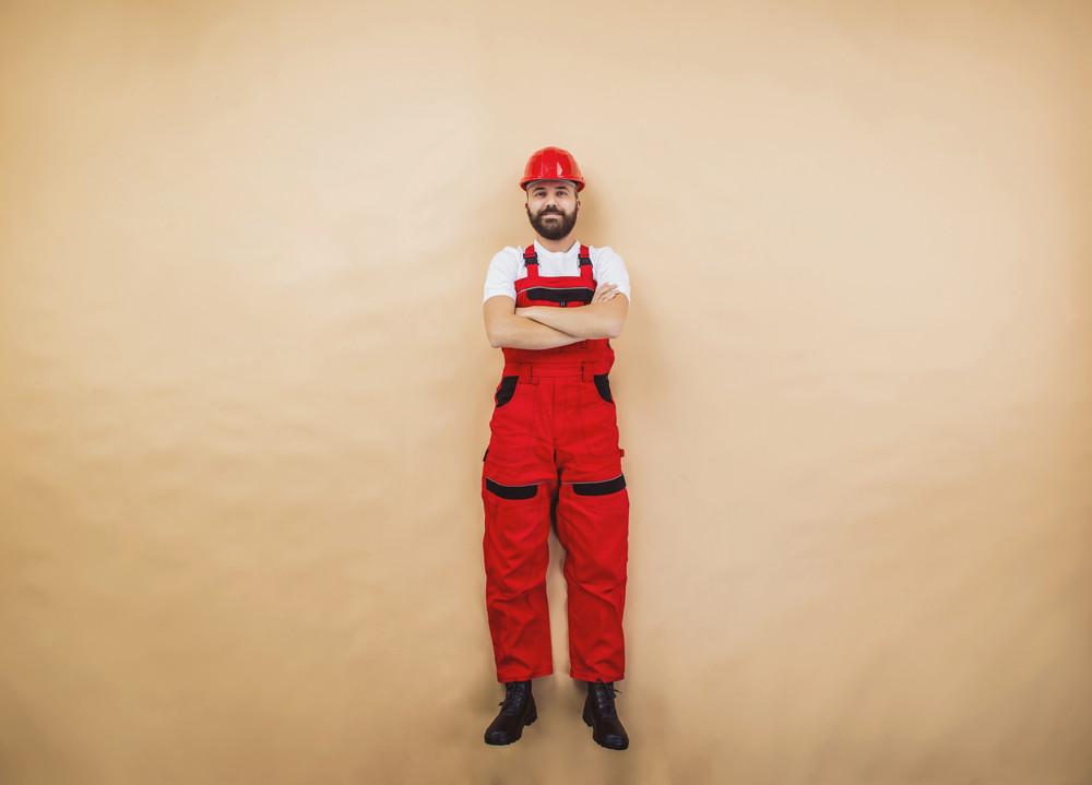 Funny construction worker is posing in studio