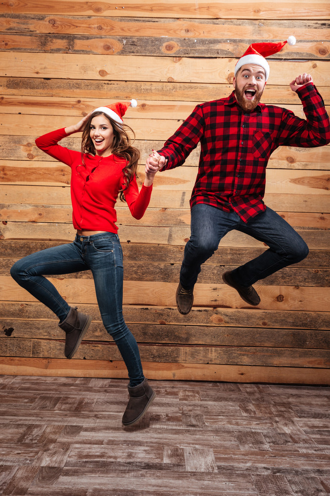Funny friends in santa's hats. full length. wooden background