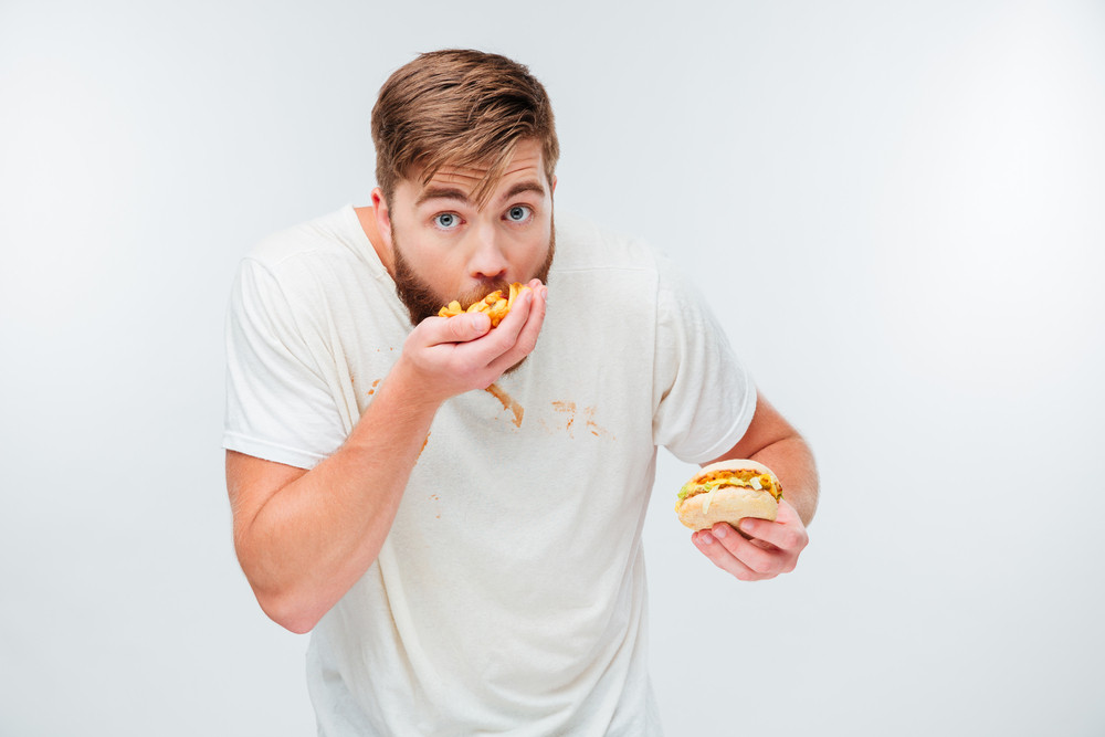 Funny hungry bearded man eating junk food isolated on white background