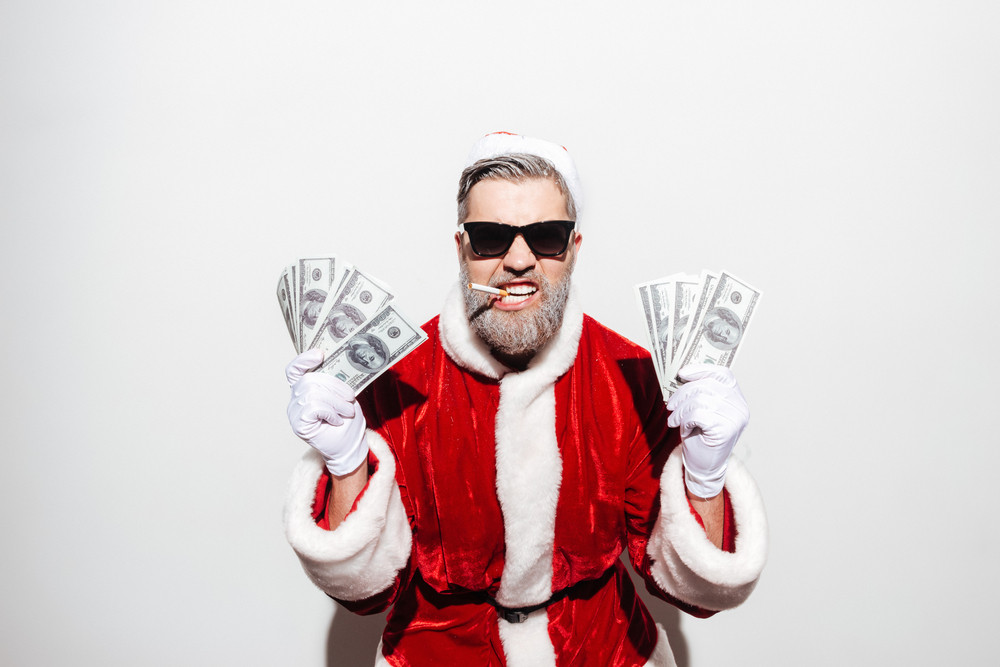 Funny man santa claus in sunglasses smoking and holding money