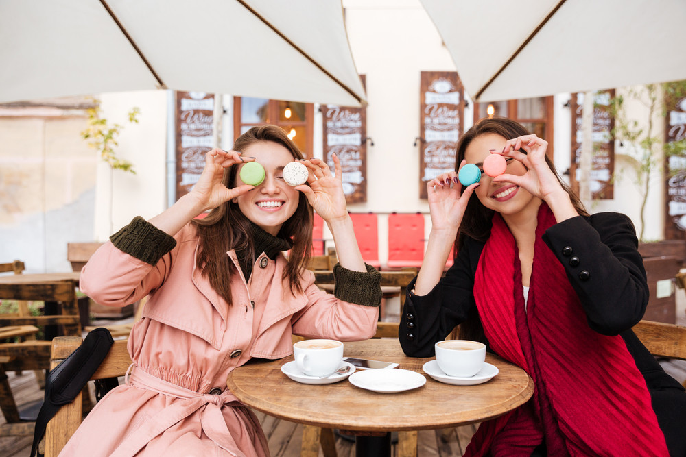 Funny models in coats at cafe. with macarons