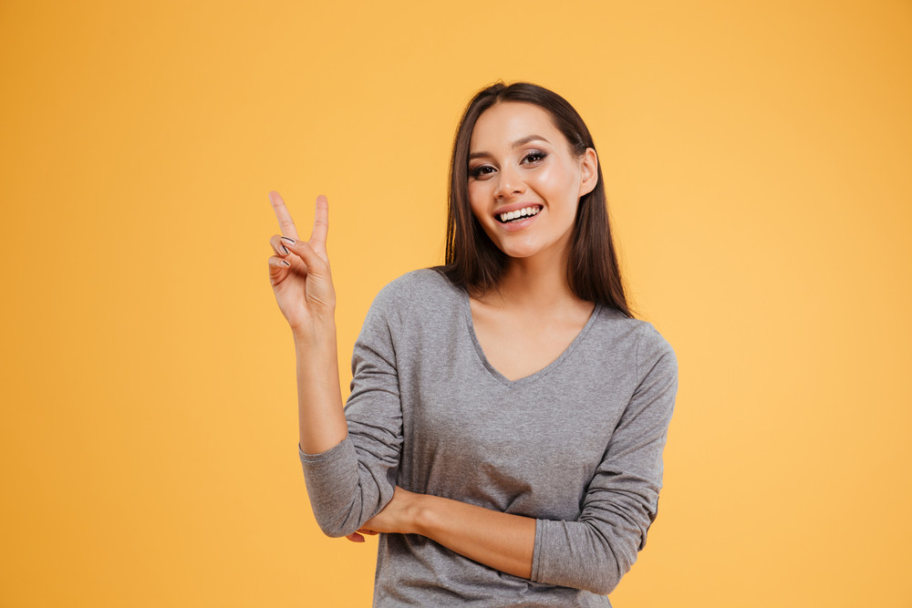 Funny woman in studio showing peace. isolated orange background