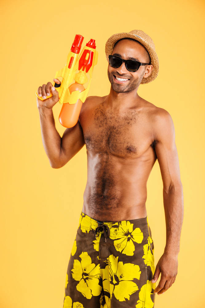 Funny young afro american man in swimwear holding water gun over orange background