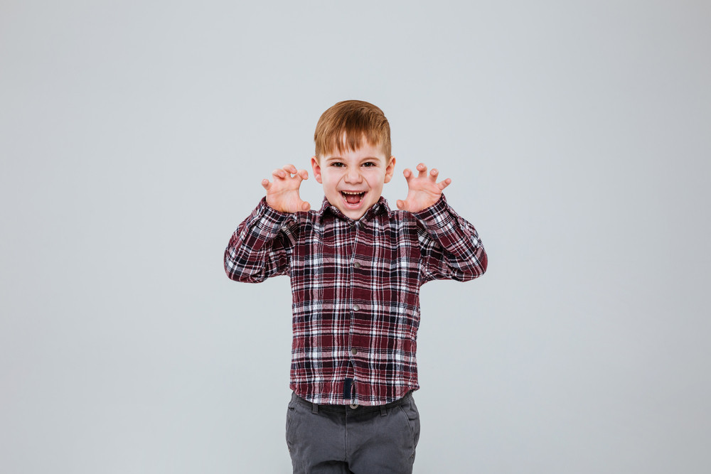 Funny young boy in shirt showing funny gestures in studio. Isolated gray background