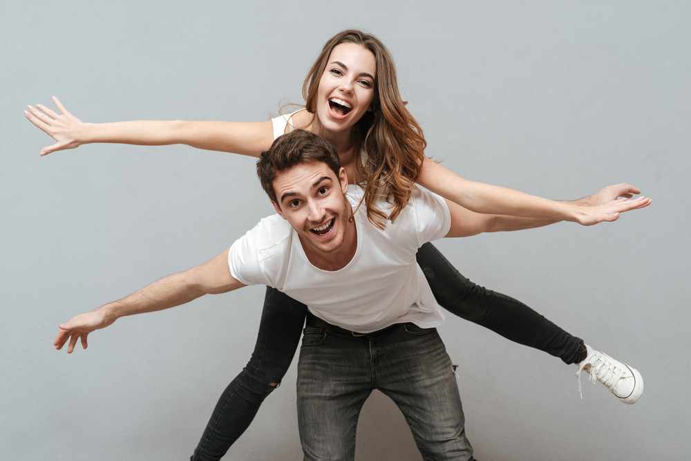 Funny Young Couple Posing In Studio. Isolated Gray