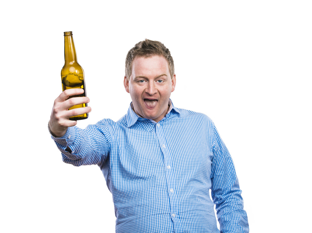 Funny young drunk man holding a beer bottle. Studio shot on white background.