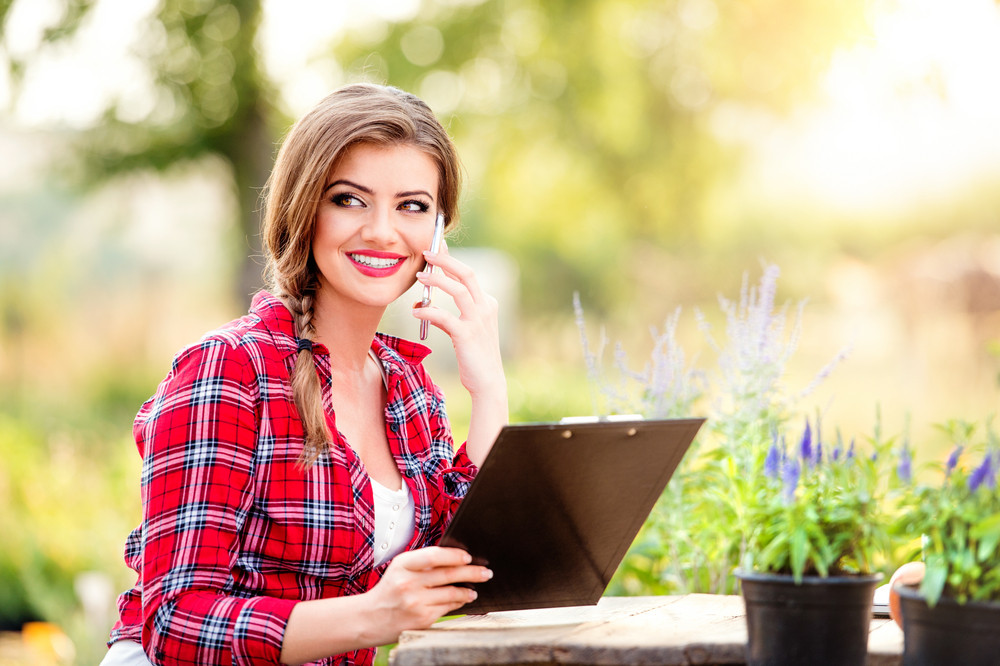Gardener sitting at the table, holding clipboard, making phone call, green sunny nature
