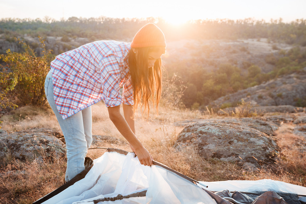 Girl collect tent on mountain