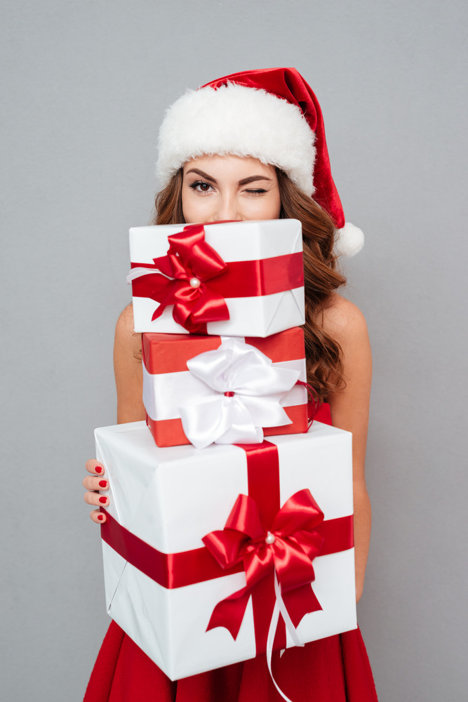 Girl hiding behind christmas gifts and winks. Santa's helper. Dress and Santa's hat