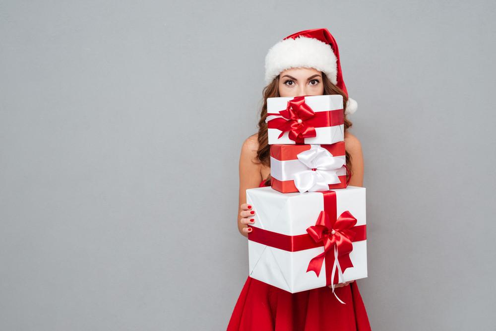 Girl hiding behind christmas gifts. Santa's helper. Dress and Santa's hat