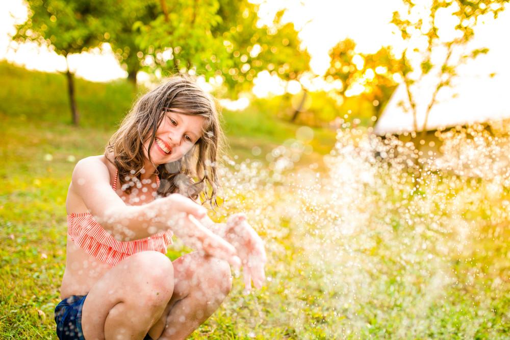 Girl in bikini sitting at the sprinkler, green sunny summer garden