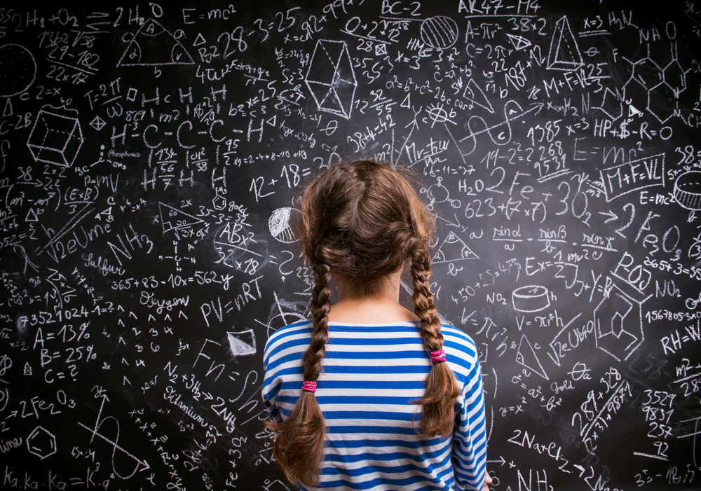 Girl  in blue striped t-shirt with two braids against big blackboard with mathematical symbols and formulas, back view, rear viewpoint