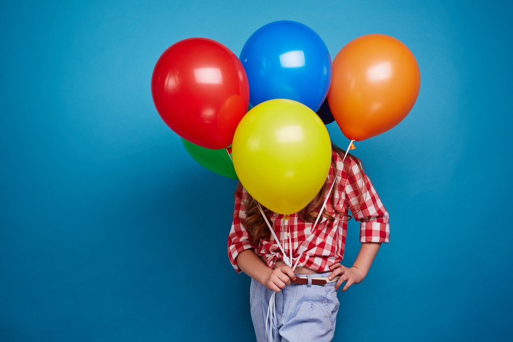 Girl in casualwear showing multi-color balloons