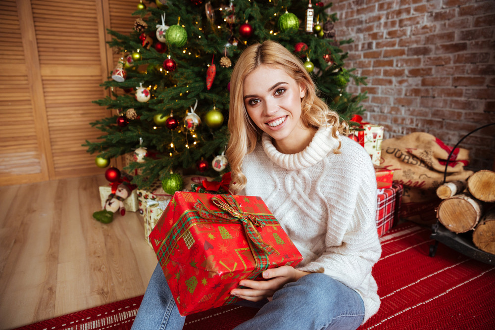 girl in sweater sitting on the floor with gift near the fir tree
