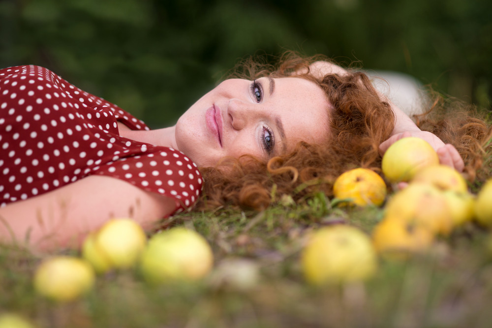 Girl with apple is lying in the garden.