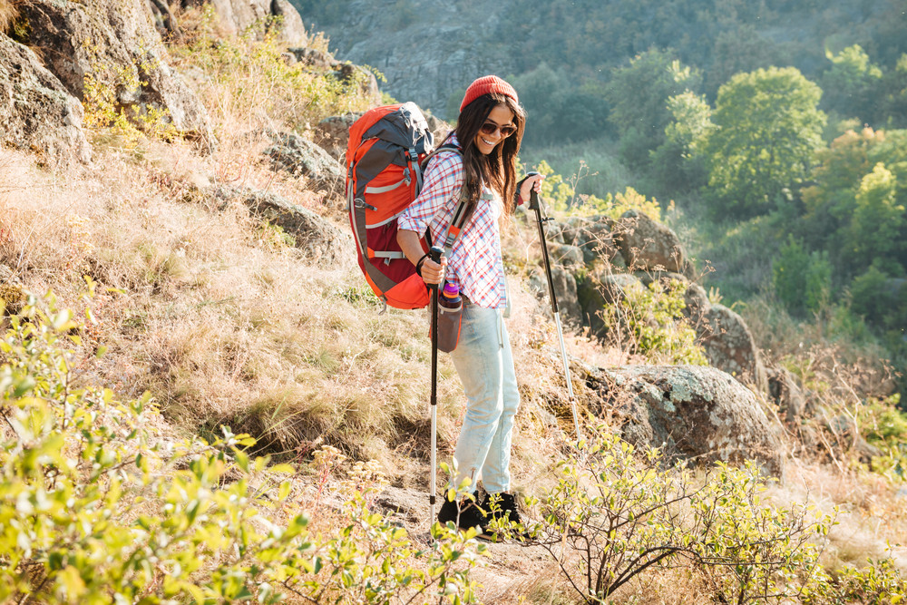 Girl with backpack and ski pole near the canyon full length image