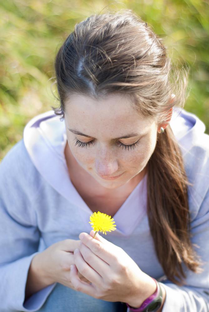 Girl with flower is enjoying sunshine.