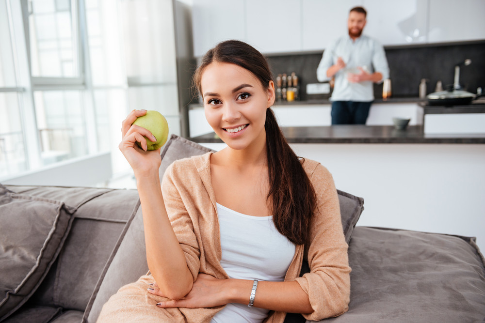 Girl with man on background. girl on bed with apple. man in kitchen