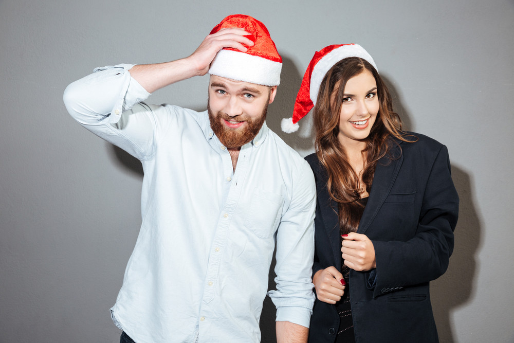 Glad christmas couple. in christmas hats. looking at camera