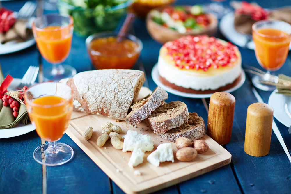 Glasses with juice, dessert, nuts and cut fresh bread on dinner table