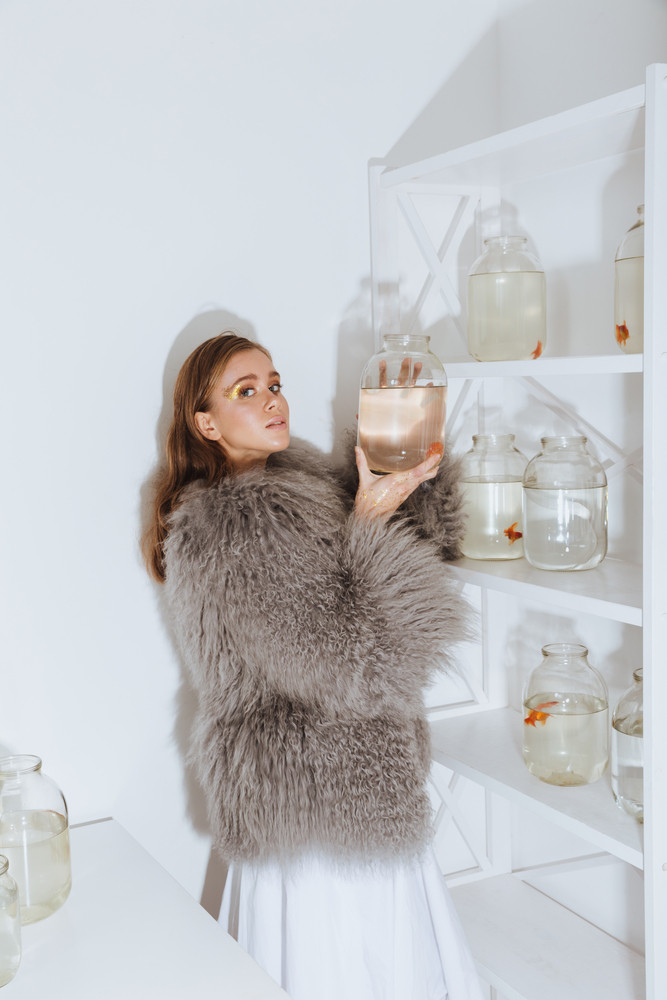 Gorgeous young woman in fur coat takind jar with gold fish from the shelf in the room