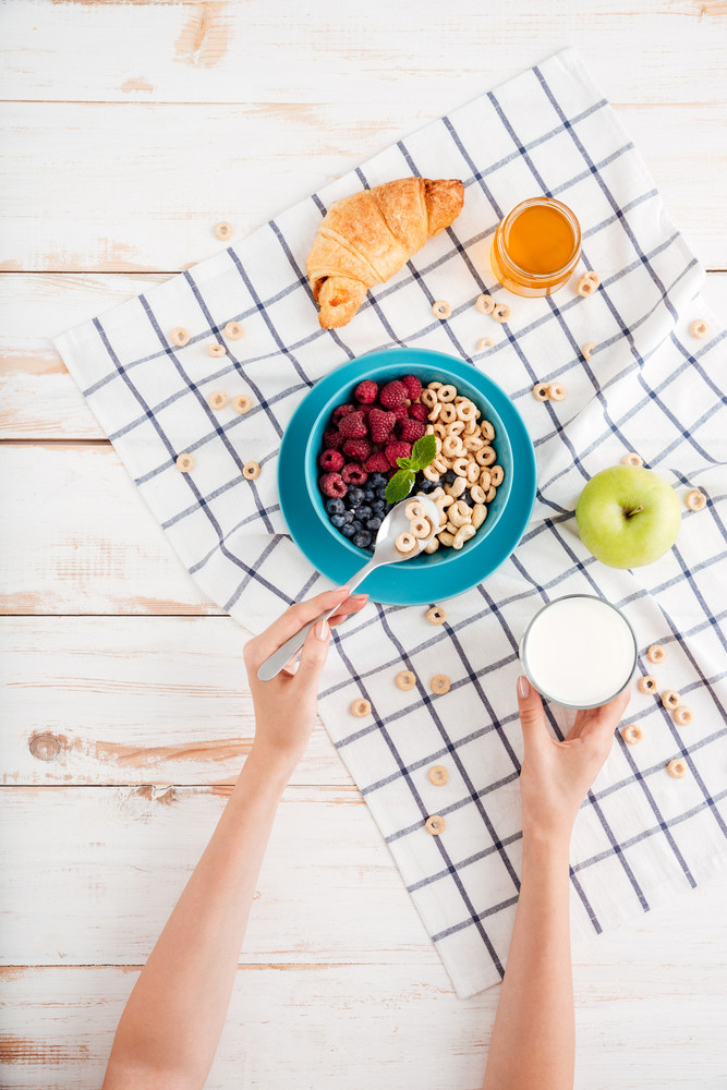 Granola, berries, apple and croissant and plaid napkin on wooden background