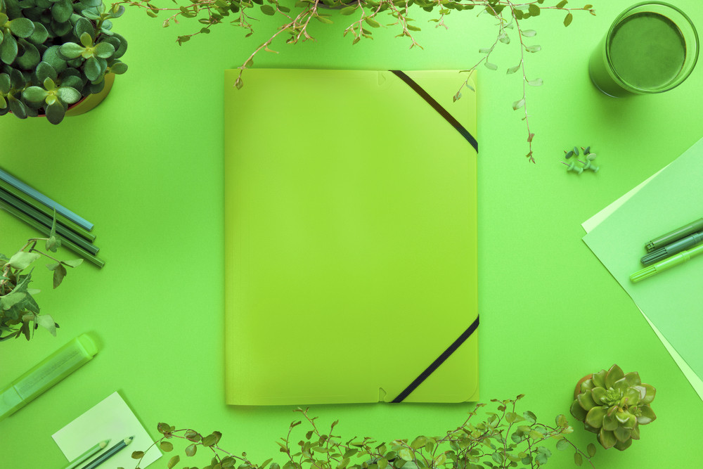 Green Concept of a Folder And Office Supplies On Desk