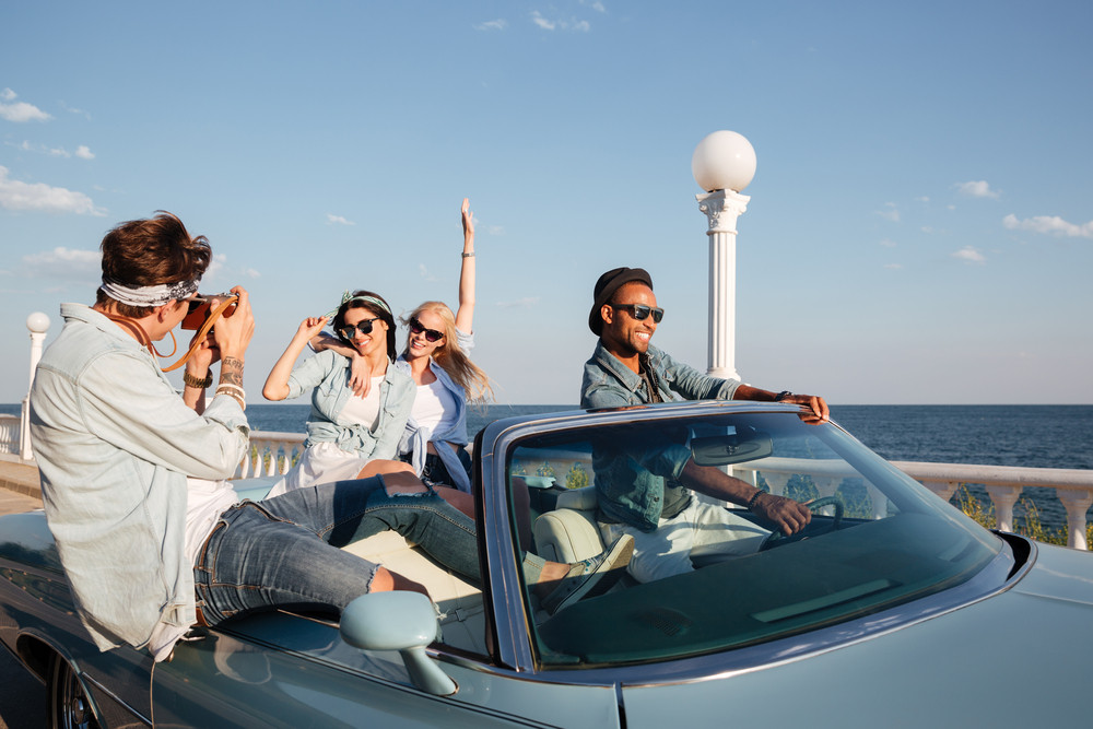 Group of cheerful young people driving a car and talking photos