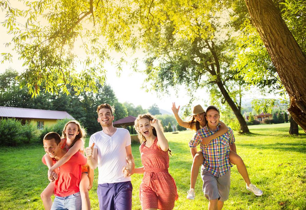 Group of five teenage friends having fun in park