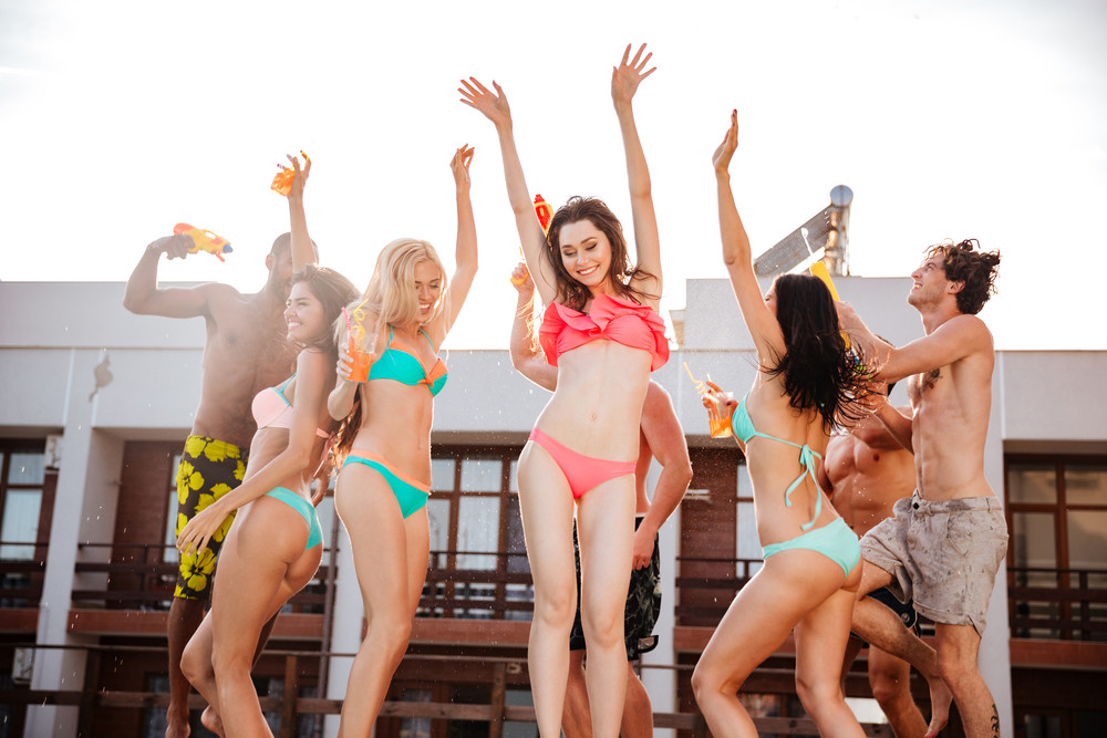 Group of happy carefree young people dancing in swimsuits in summer