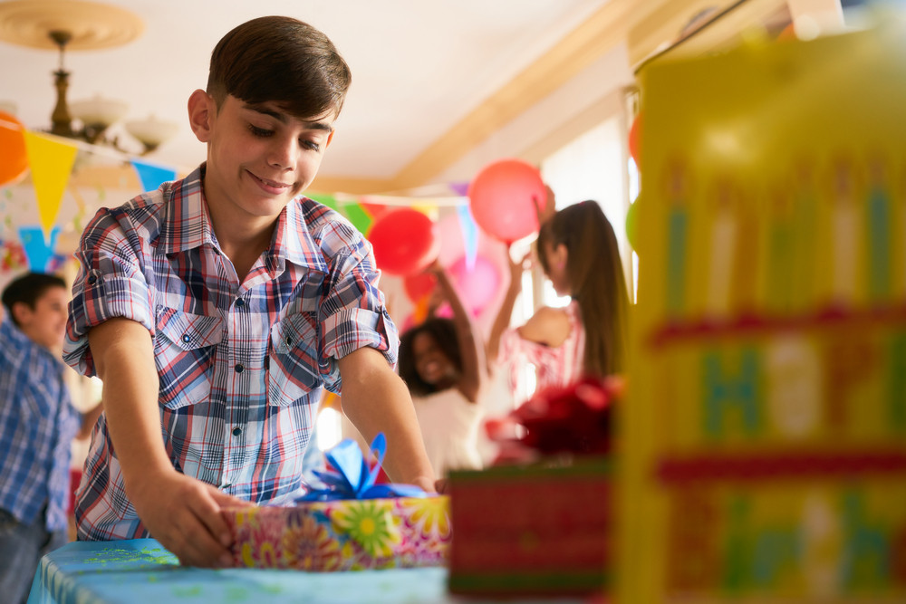 Group of happy children celebrating birthday at home, kids and friends having fun at party. Hispanic boy putting present on the table with other gifts.