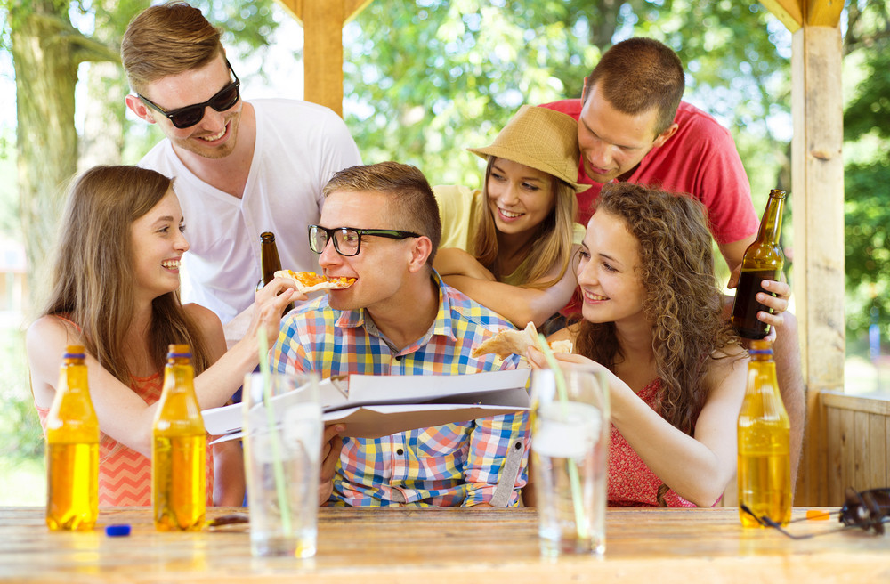 Group of happy friends drinking and eating pizza in pub garden