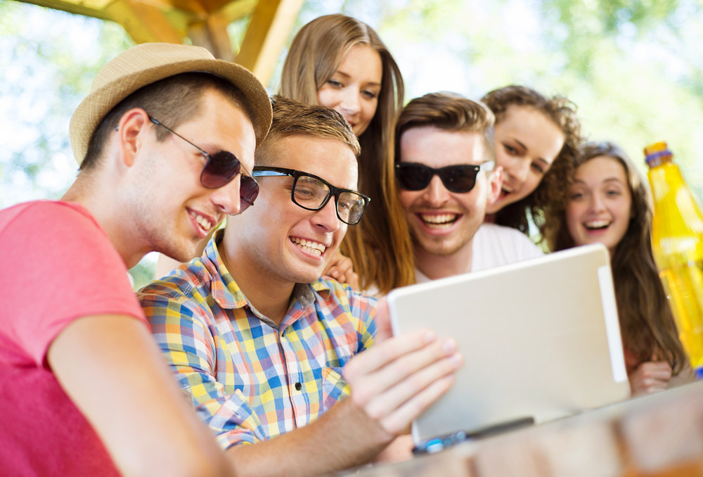 Group of happy friends drinking and having fun with tablet in pub garden