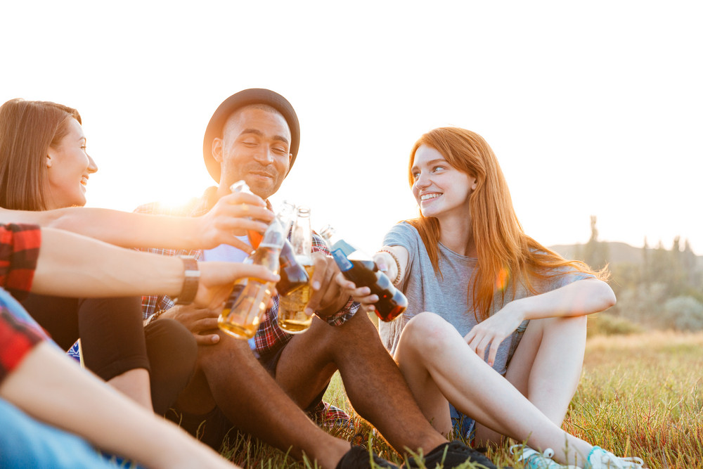 Group of happy young friends sitting and drinking beer and soda outdoors