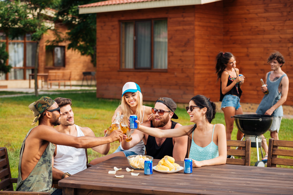 Group of happy young people celebrating and drinking outdoors