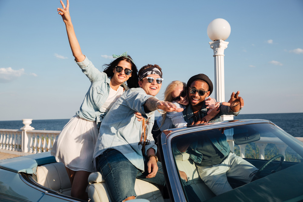 Group of happy young people driving car near the sea