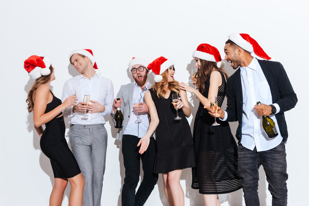 Group of happy young people in santa claus hats celebrating new year and having fun over white background