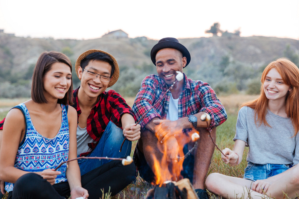 Group of happy young people sitting and roasting marshmallows on campfire outdoors