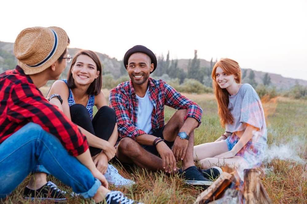 Group of happy young people sitting near campfire together