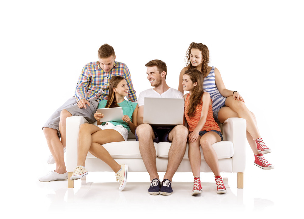 Group of happy young people sitting on sofa and using digital tablet and laptop, isolated on white background. Best friends