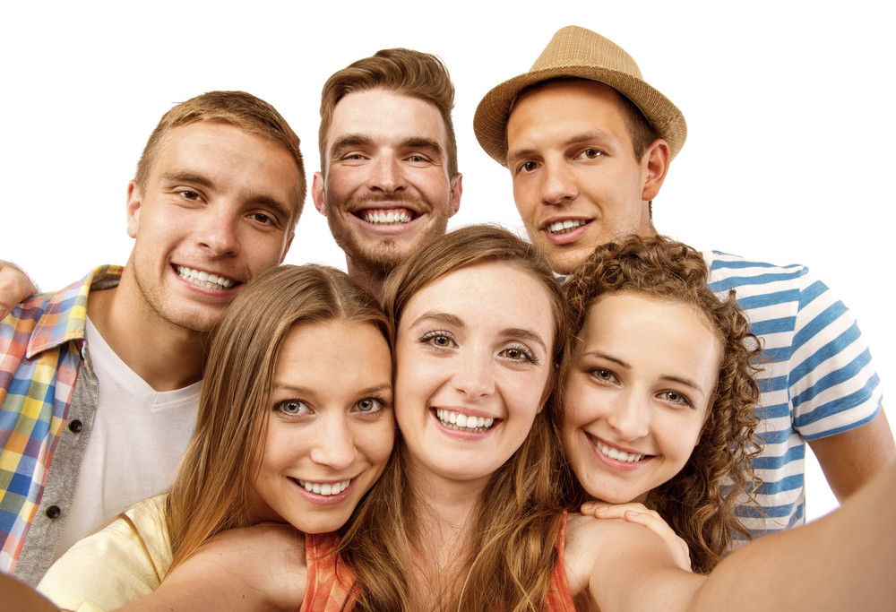 Group of happy young teenager students taking selfie photo isolated on white background