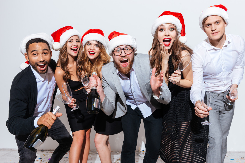 Group of people in santa claus hats with bottle of champagne having fun over white background