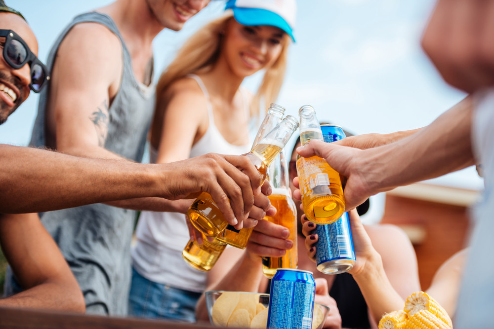 Group of people with beer and soda celebrating outdoors together