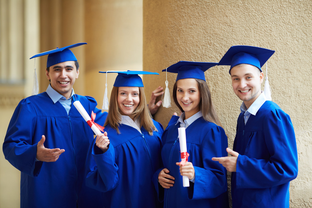 Group of smart students in graduation gowns looking at camera ...