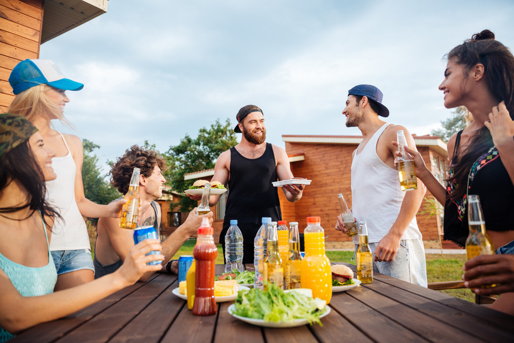 Group of smiling joyful young people eating and drinking at the table outdoors
