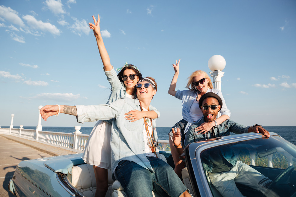 Group of smiling young friends driving car near the sea and having fun